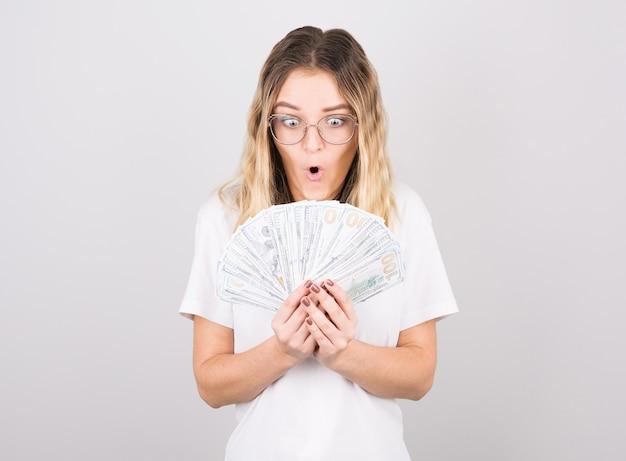 Junge schöne kaukasische frau schockiert durch den gewinn der lotterie