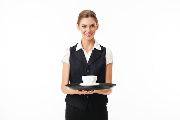 Junge schöne kellnerin in uniform, die tablett mit tasse kaffee hält, während glücklich
