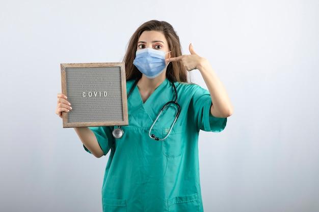 Junge schöne krankenschwester in medizinischer maske mit einem rahmen, der auf medizinische maske zeigt