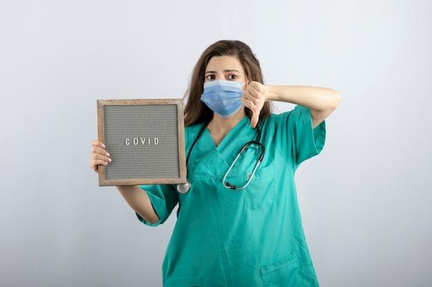 Junge schöne krankenschwester in medizinischer maske mit einem rahmen, der einen daumen nach unten zeigt
