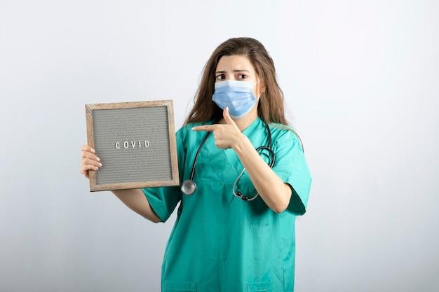 Junge schöne krankenschwester in medizinischer maske mit stethoskop, das auf einen rahmen zeigt