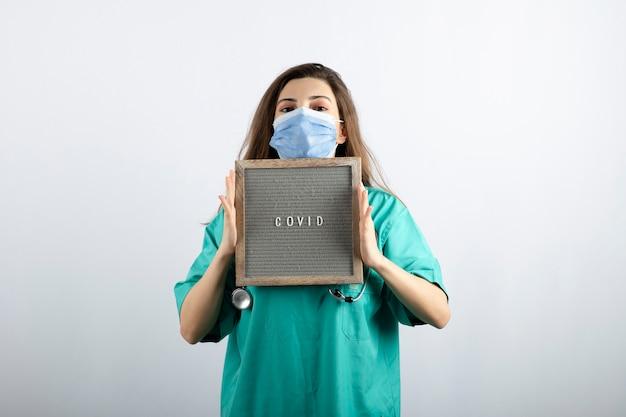 Junge schöne krankenschwester in medizinischer maske mit stethoskop, das einen rahmen hält