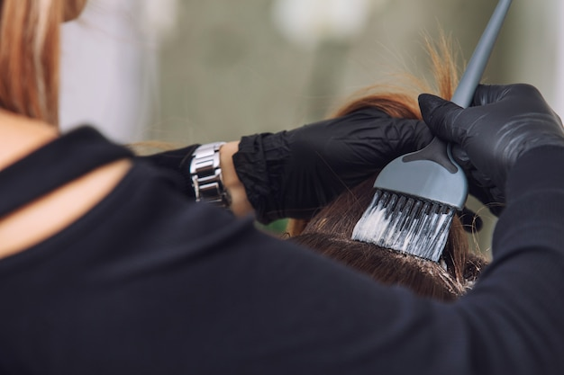 Junge schöne kundenhaarfärbung von einem professionellen friseur in einer schönheitssalon-nahaufnahme