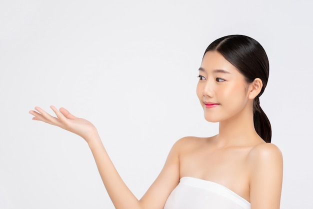 Junge schöne lächelnde asiatin, die offene hand für schönheitskonzepte ausdrückt