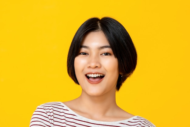 Junge schöne lächelnde asiatische frau im gelben hintergrund