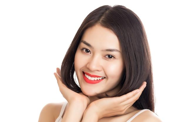 Junge schöne lächelnde asiatische frau mit hand, die ihr haar lokalisiert auf weiß berührt.