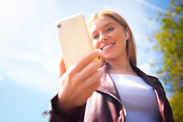 Junge schöne lächelnde erwachsene kaukasische mädchen verwischen gesicht im freien im park mit chat-kommunikation mit handy