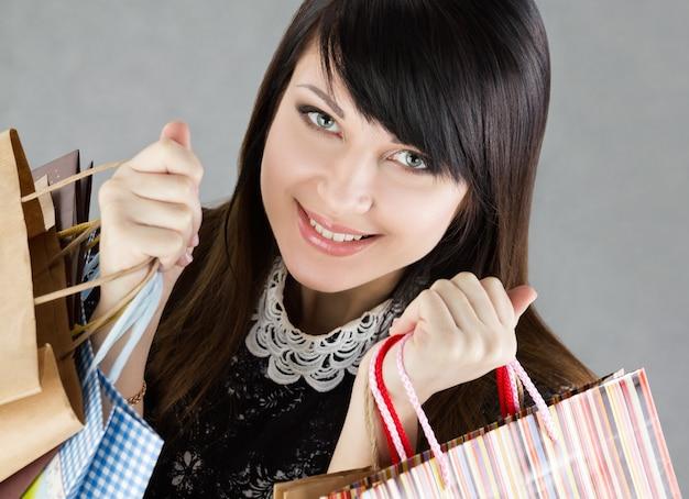 Junge schöne lächelnde frau, die papiertüten mit einkäufen hält. verkaufs- und einkaufskonzept Premium Fotos