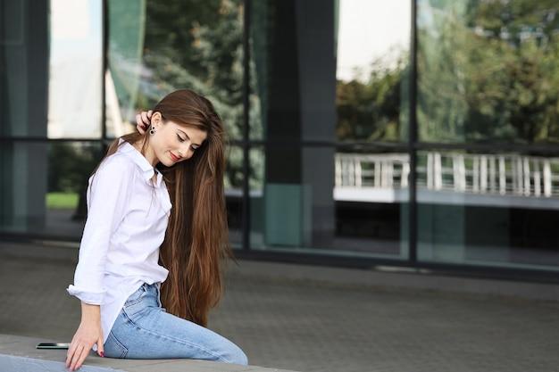Junge schöne lächelnde frau in freizeitkleidung glättet ihr langes haar