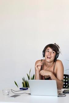 Junge schöne lächelnde frau mit den kopfhörern, die das arbeiten mit laptop auf tabelle sitzen