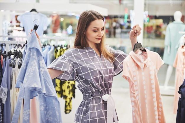 Junge schöne lächelnde frau trifft wahl beim einkaufen in einem geschäft