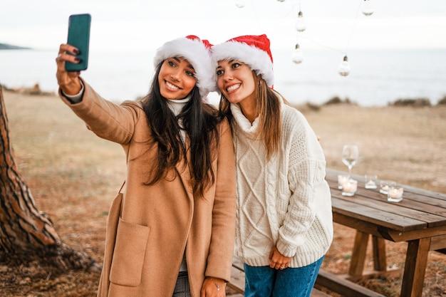 Junge schöne lächelnde freundinnen der gemischten rasse, die ein selbstporträt machen, das ihr telefon im freien mit weihnachtsmannhut betrachtet