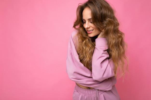 Junge schöne lockige blonde frau mit sexy ausdruck, fröhlichem und glücklichem gesicht mit trendigem rosa pullover einzeln auf rosafarbenem hintergrund mit kopierraum