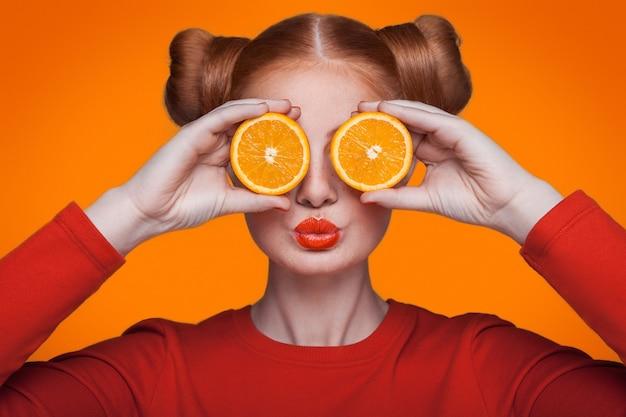 Junge schöne lustige mode-modell mit orangenscheibe auf orangem hintergrund. mit orangem make-up und frisur und sommersprossen. hält orange zwischen den augen mit kuss.