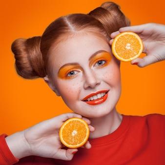 Junge schöne lustige mode-modell mit orangenscheibe auf orangem hintergrund. mit orangem make-up und frisur und sommersprossen. studioaufnahme, blick in die kamera mit einem lächeln.