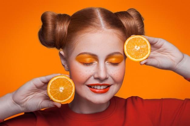 Junge schöne lustige mode-modell mit orangenscheibe auf orangem hintergrund. mit orangem make-up und frisur und sommersprossen. studioaufnahme, blick in die kamera mit geschlossenen augen und lächelnd.