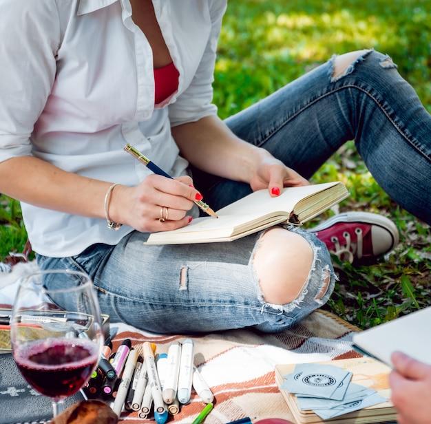 Junge schöne mädchen, die die bilder im skizzenbuch zeichnen. im park