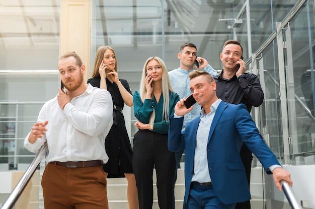 Junge schöne menschen männer und frauen bei der arbeit telefonisch anrufen