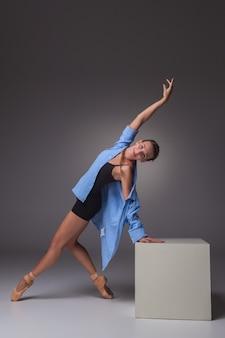 Junge schöne moderne arttänzerin, die auf weißem würfel auf einem grauen hintergrund des studios aufwirft