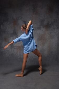 Junge schöne moderne arttänzerin in einem blauen hemd, das auf einem grauen hintergrund des studios aufwirft
