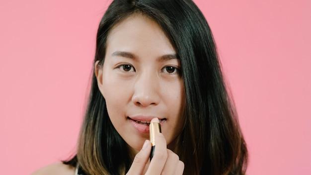 Junge schöne moderne asiatin, die lippenmake-up mit kosmetischer bürste in der freizeitbekleidung über rosa hintergrundatelieraufnahme anwendet.