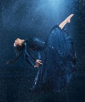 Junge schöne moderne tänzerin, die unter wassertropfen tanzt