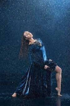 Junge schöne moderne tänzerin tanzen unter wassertropfen