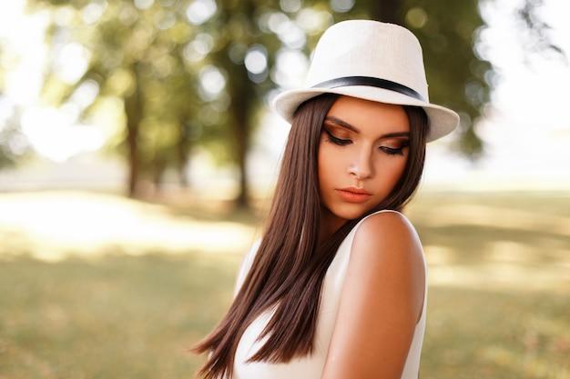 Junge schöne modische frau im weißen stilvollen kleid mit hut auf natur