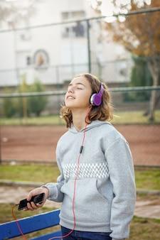 Junge schöne modische teenager-mädchen hört musik auf kopfhörern von einem smartphone