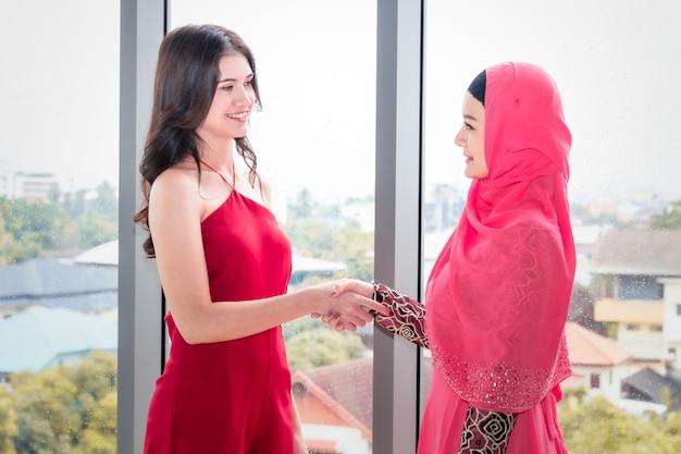 Junge schöne moslemische frau, die hand mit kaukasischen freundschaften rüttelt