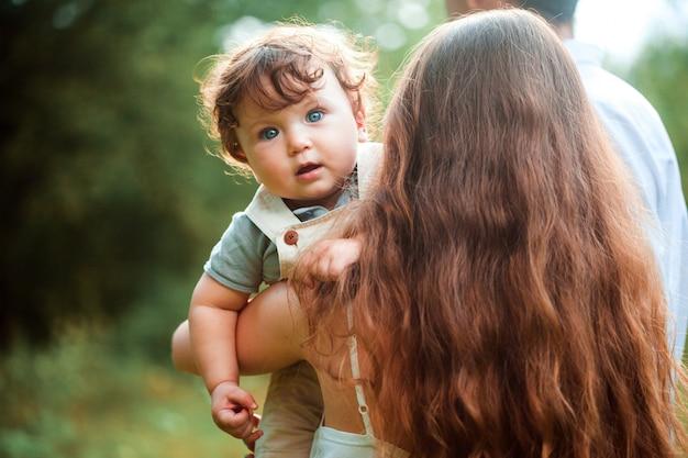 Junge schöne mutter, die ihren kleinen kleinkindsohn gegen grünes gras umarmt. glückliche frau mit ihrem baby an einem sonnigen tag des sommers. familie zu fuß auf der wiese.