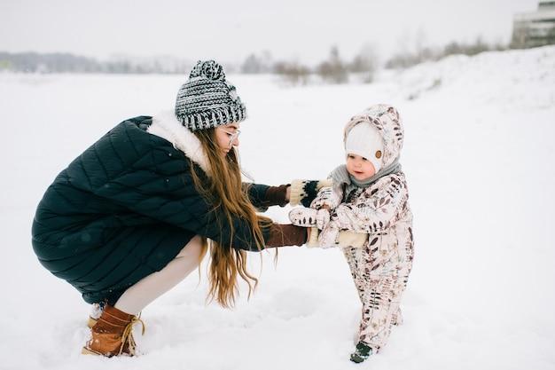 Junge schöne mutter, die mit der kleinen tochter im winter im freien spielt. glückliche fröhlich lächelnde frau mit reizendem kind haben spaß im schnee. mutterschaft und kindheit.