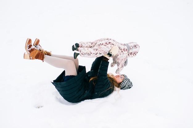 Junge schöne mutter, die mit der kleinen tochter im winter im freien spielt. glückliche fröhlich lächelnde frau mit reizendem kind haben spaß im schnee.