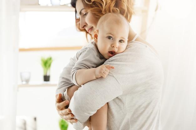 Junge schöne mutter hält ihren kleinen neugeborenen sohn und beruhigt ihn nach bösen träumen. süße szene der mutterschaft. familien- und lifestyle-konzept.