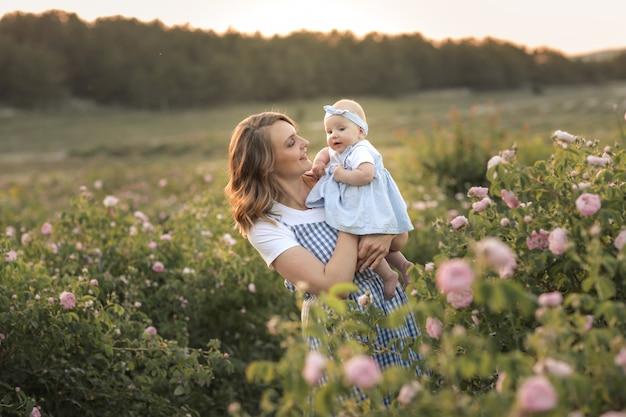 Junge schöne mutter mit einem kind steht in einem landwirtschaftlichen feld mit einer blühenden rose
