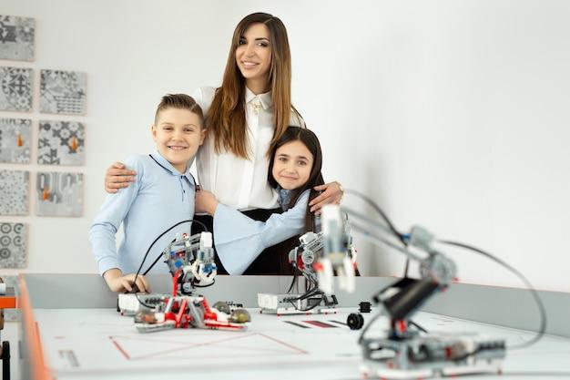 Junge schöne mutter mit ihrem sohn und ihrer tochter posieren an der robotikschule mit robotern