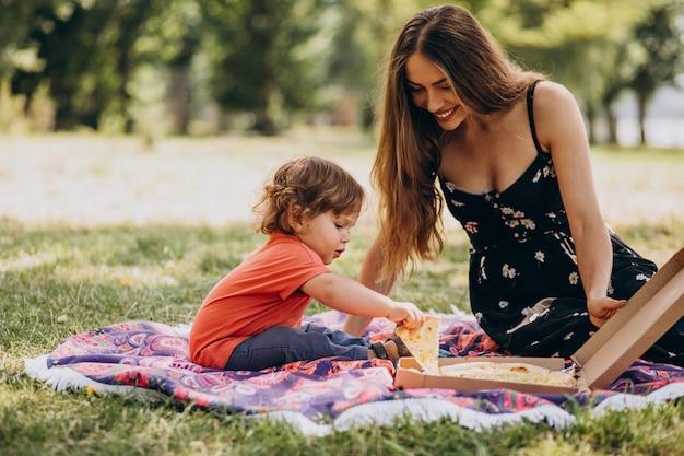 Junge schöne mutter mit kleinem jungen essen pizza im park