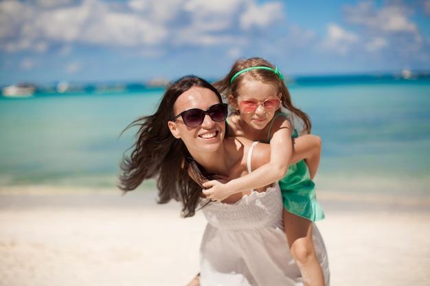 Junge schöne mutter und ihre entzückende kleine tochter haben spaß am tropischen strand