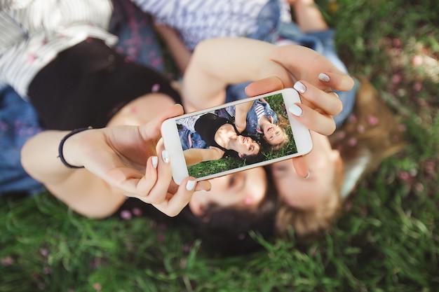 Junge schöne mutter und ihre kleine tochter, die selfie am handy macht. mama und ihr baby, die draußen spaß im park haben. mädchen, die bild am handy und am lächeln machen