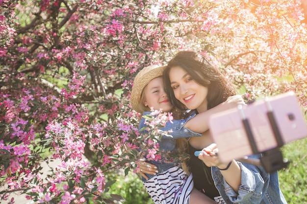 Junge schöne mutter und ihre kleine tochter, die selfie am handy macht.
