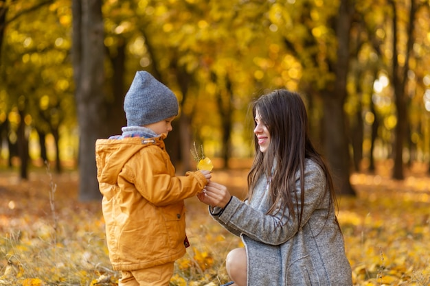Junge schöne mutter verbringt zeit mit ihrem geliebten kleinen sohn im herbstpark spazieren.