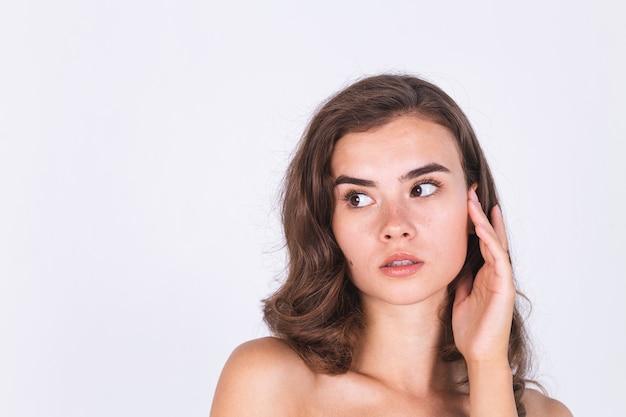 Junge schöne natürliche weiche saubere hautfrau mit sommersprossen hellem make-up auf weißer wand mit bloßen schultern