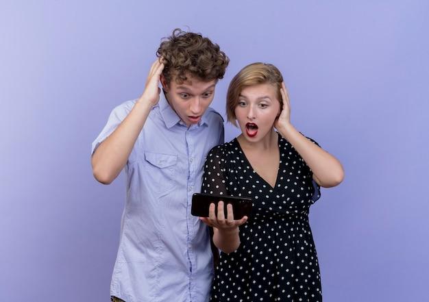 Junge schöne paar mann und frau betrachten bildschirm des smartphones überrascht und erstaunt über blaue wand stehen