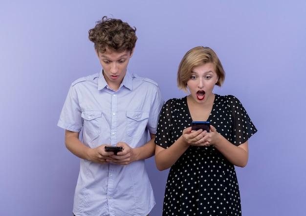 Junge schöne paar mann und frau, die ihre smartphones betrachten, überrascht, über blauer wand stehend