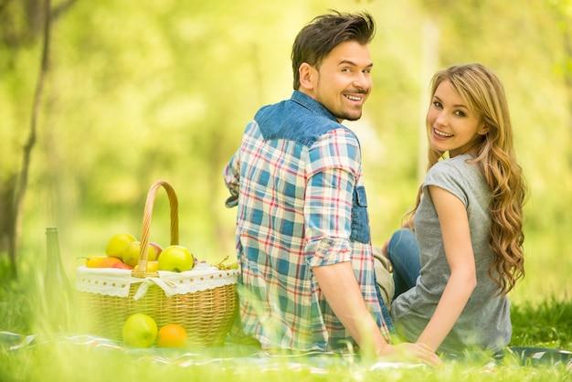 Junge schöne paare auf romantischem picknick im holz.