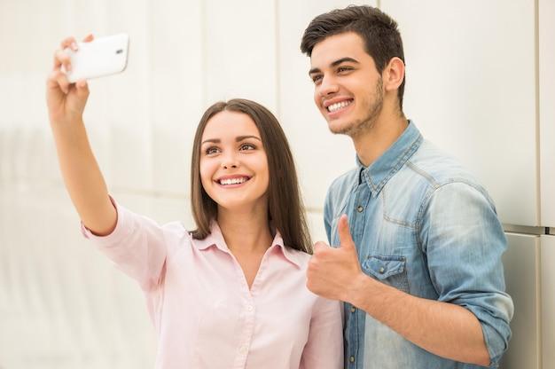 Junge schöne paare, die selfie mit intelligentem telefon nehmen.