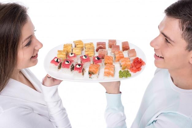 Junge schöne paare essen sushi zusammen.