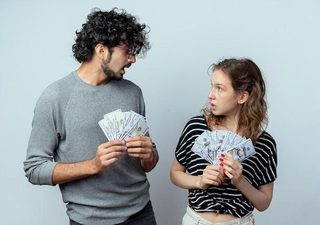 Junge schöne paare mann und frauen, die bargeld halten, die einander überrascht stehen, stehen über weißer wand