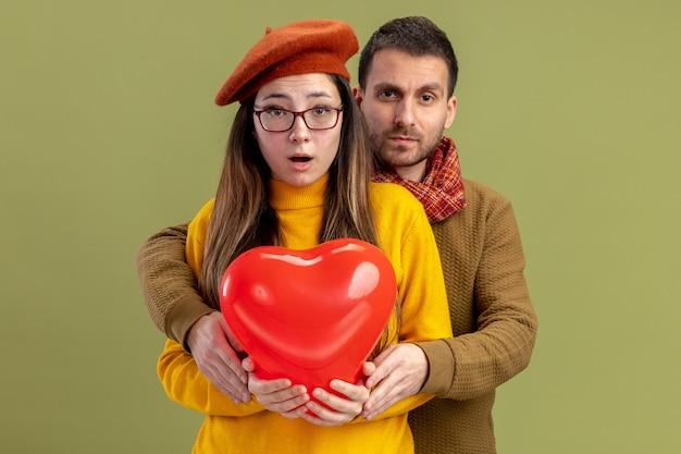 Junge schöne paarfrau in baskenmütze mit herzförmigem ballon und mann mit schal um den hals überrascht, valentinstag zu feiern, der über grüner wand steht