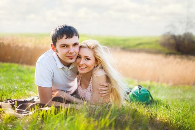 Junge schöne paarfrau und -mann, die auf gras liegen und über sommerlandschaft lächeln